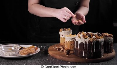 Baker / pastry chef (woman) prepares holiday bread for Easter and decorates with nuts, dried fruits, white chocolate frosting