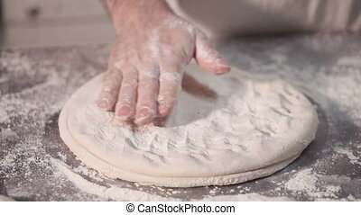 Baker preparing a round bread dough, rotating and kneading...