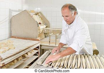 Baker preparing baguettes