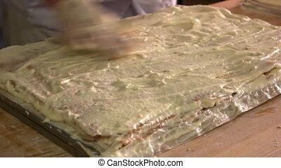 Baker preparing napoleon cake. Layered cake with mustard...