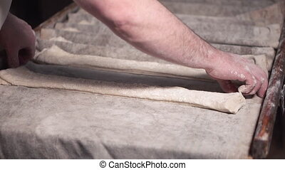 Baker preparing rows of uncooked dough loaf in bakery...