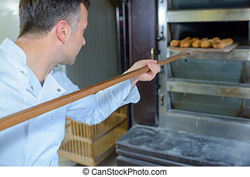 Baker removing bread from oven