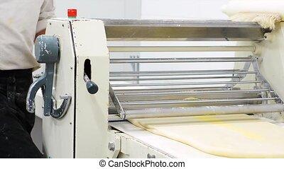 Baker using dough sheeter machine to produce croissants...