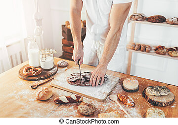 Baker with a variety of delicious freshly baked bread and pastry