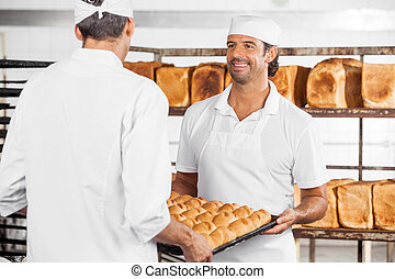 Baker With Colleague Carrying Bread Loaves In Tray