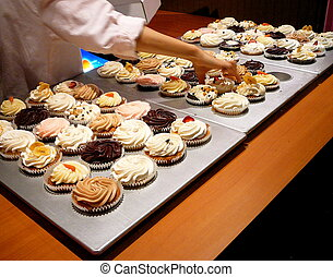 Baker With Cupcakes - Baker Reaches For Cupcake in Gourmet...