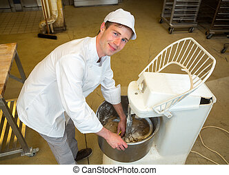 Baker with dough kneading machine in bakery