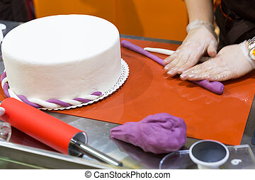Baker with gum paste - Baker hands decorating cake with gum...