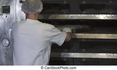 Bakers load bread dough into oven - Bakers load bread dough...