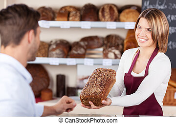 Smiling friendly young bakery assistant selling bread showing a wholewheat loaf to a male customer