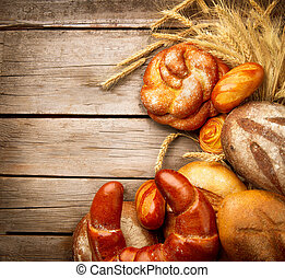 Bakery Bread and Sheaf over Wood Background