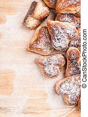 bakery hearts from split pastry with sugar powder on wooden...