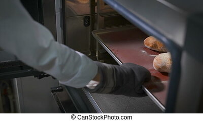 Bakery, on whose hand the special thick gloves, pulls out of the oven tray with freshly baked bread and a small cut in the middle