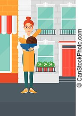 Bakery owner with bread. - A woman holding a bowl with bread...