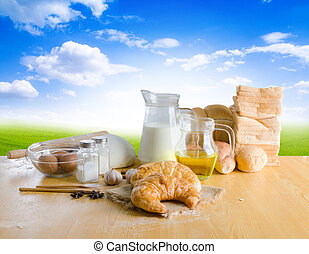 Bakery product and ingredients on wooden table over green field and blue sky