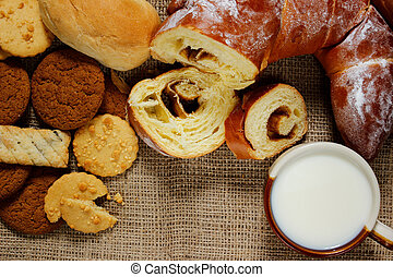 Bakery product assortment with bread loaves, buns, rolls and sweet pastries with a mug of milk