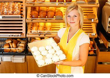 Bakery shopkeeper presents meringue - Bakery shopkeeper with...