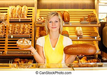 Bakery shopkeeper with two loafs of bread - Shopkeeper in ...