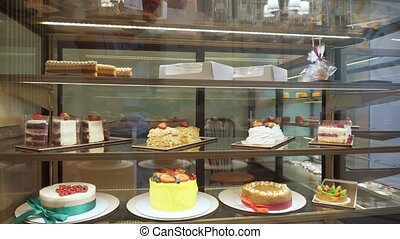 Bakery vitrine with cakes and pastries on glass shelves. -...