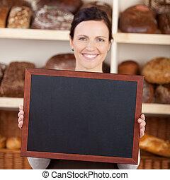 Bakery worker holding a blank chalkboard - Beautiful smiling...