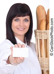 bakery worker holding out business card