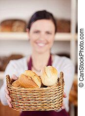 Bakery worker offering a basket of rolls