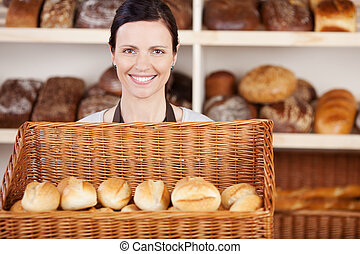 Bakery worker with a basket of rolls