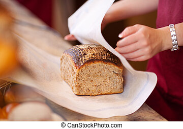 Bakery Worker Wrapping Bread At Counter