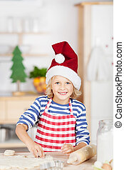 Smiling pretty little blond girl baking cookies during Advent standing at a kitchen counter in a red striped apron and Santa hat