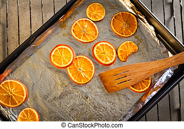 Baking fresh orange slices, to dry them for Christmas decoration.