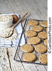 Baking grid with fresh oat cookies on rustic wooden table background, ingredients and kitchen utensil.