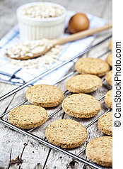 Baking grid with fresh oat cookies on rustic wooden table background, ingredients and kitchen utensil closeup.