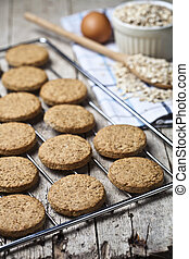 Baking grid with fresh oat cookies on rustic wooden table background, ingredients and kitchen utensil closeup on rustic wooden table.