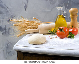 baking ingredients - dough, rolling-pin, olive oil tomatoes...