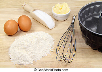 Baking ingredients with eggbeater and cake pan on a wooden kitchenboard