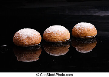 Baking on a black background. White buns sprinkled with powder and flour.