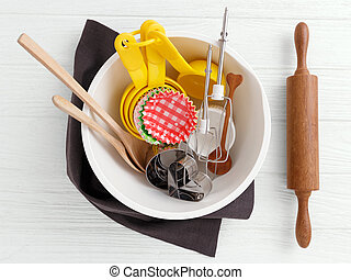 Baking tools and utensils in mixing bowl on white wooden...