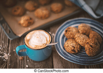 Baking tray and a plate of oatmeal cookies on the wooden table