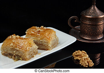 Baklava on a plate next to a cup of coffee