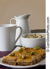 Baklava on a Plate with a Bowl of Pistachios and Cup and Mug