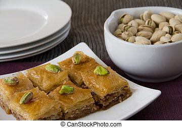 Baklava on a Plate with a Bowl of Pistachios and Plates