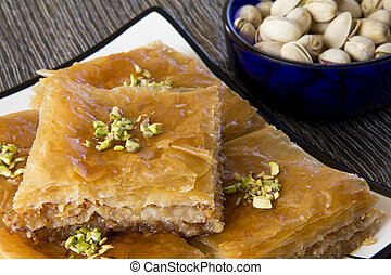 Baklava on a Plate with a Bowl of Pistachios