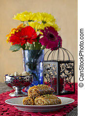 Baklava on a Table with Nuts and Flowers