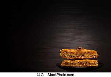 Baklava with honey on a black background, traditional Turkish sweets. Copy space
