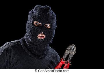 Balaclava and shears - a burglar wearing a balaclava holding...