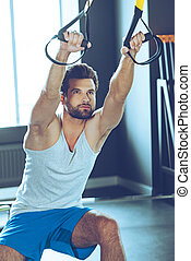 Balance and concentration. Young handsome man in sportswear exercising at gym