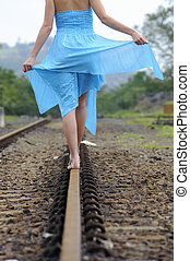 Girl in blue dress walks along the tracks on a summer day