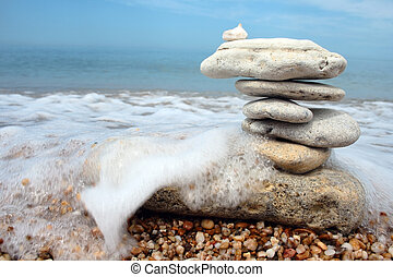 balance in danger - balanced stones in danger against sea...