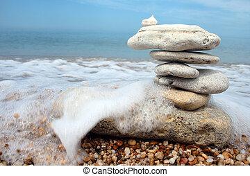 balance in danger - balanced stones in danger against sea...