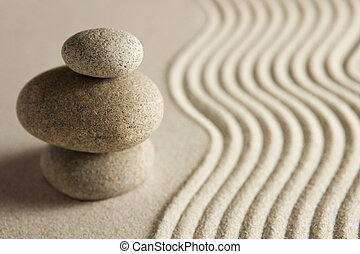 Balance - Stacked stones on sand background; zen concept